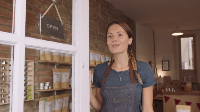 portrait of pretty female retail store owner entrepreneur opening door with open sign and looking outside - store opening stock videos & royalty-free footage