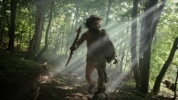 Portrait of Primeval Caveman Wearing Animal Skin and Fur Hunting with a Stone Tipped Spear in the Prehistoric Forest. Primitive Neanderthal Hunter Ready to Throw Spear in the Jungle