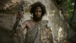 Portrait of Primeval Caveman Wearing Animal Skin Holding Stone Tipped Hammer. Prehistoric Neanderthal Hunter Posing with Primitive Hunting in the Jungle. Looking at Camera