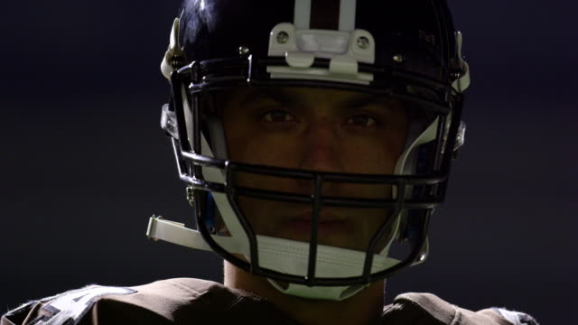 cu portrait of professional football player with helmet on before night game - football player stock videos & royalty-free footage