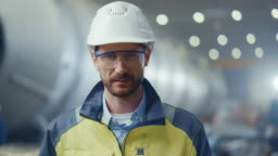 Portrait of Professional Heavy Industry Engineer / Worker Wearing Safety Uniform, Goggles and Hard Hat Smiling. In the Background Unfocused Large Industrial Factory where Welding Sparks Flying