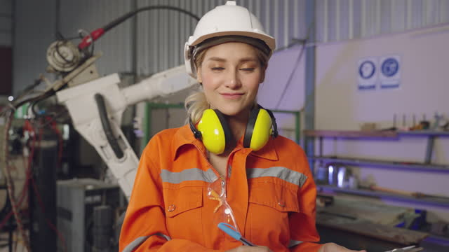portrait of professional heavy industry engineer / worker wearing safety uniform, goggles and hard hat smiling. in the background unfocused large industrial factory where welding sparks flying - welding helmet stock videos & royalty-free footage