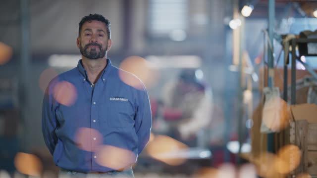 stockvideo's en b-roll-footage met slo mo portrait of proud business owner standing behind table covered with steel hammers in warehouse - scherpte verlegging