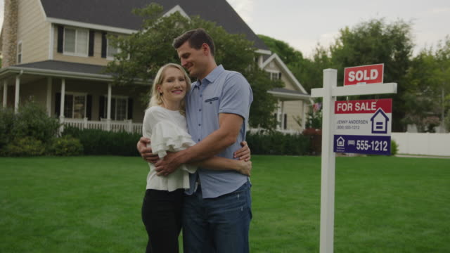 portrait of proud couple hugging on lawn of sold house for sale / pleasant grove, utah, united states - 売り出し中点の映像素材/bロール