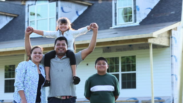ws ds portrait of proud family in front of house under construction / eastville, virginia, united states - 住宅購入点の映像素材/bロール