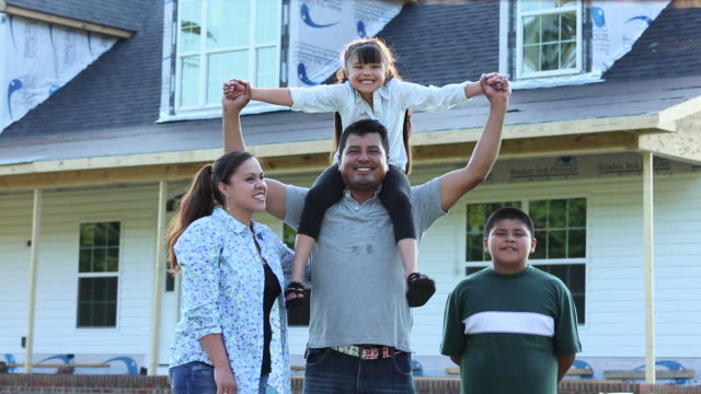 ws ds portrait of proud family in front of house under construction / eastville, virginia, united states - cultura americana video stock e b–roll