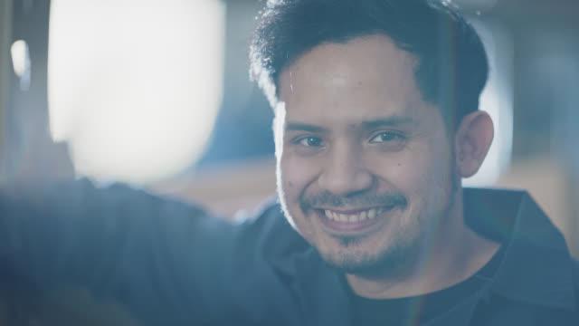 vidéos et rushes de slo mo cu portrait of proud industry worker smiling in warehouse - ouvrier
