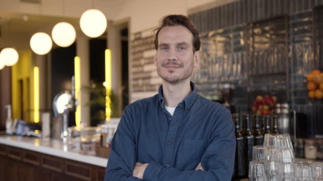 vídeos de stock e filmes b-roll de portrait of proud small business owner in cafe restaurant looking to camera - empregado de mesa