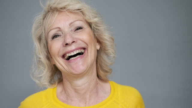 portrait of relaxed laughing blond woman in late 50s - medium length hair stock videos & royalty-free footage
