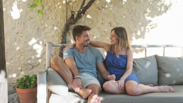 vídeos y material grabado en eventos de stock de retrato de pareja joven relajada en sofá al aire libre - pareja joven