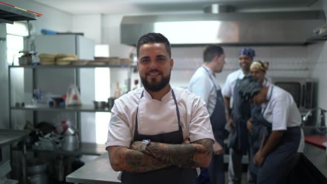 porträt des restaurantchefs mit seinem team in der küche - employee engagement stock-videos und b-roll-filmmaterial