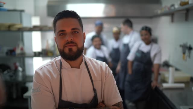 portrait of restaurant chef with his team in the kitchen - small business stock videos & royalty-free footage