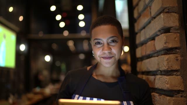 vídeos de stock, filmes e b-roll de retrato do proprietário do restaurante que olha a câmera e que prende uma tabuleta digital - povo brasileiro