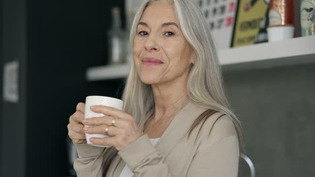 stockvideo's en b-roll-footage met portret van teruggetrokken vrouw die van de koffie van de ochtend geniet - koffiekop