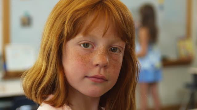cu portrait of schoolgirl (8-9) in classroom, manchester, vermont, usa - allvarlig bildbanksvideor och videomaterial från bakom kulisserna