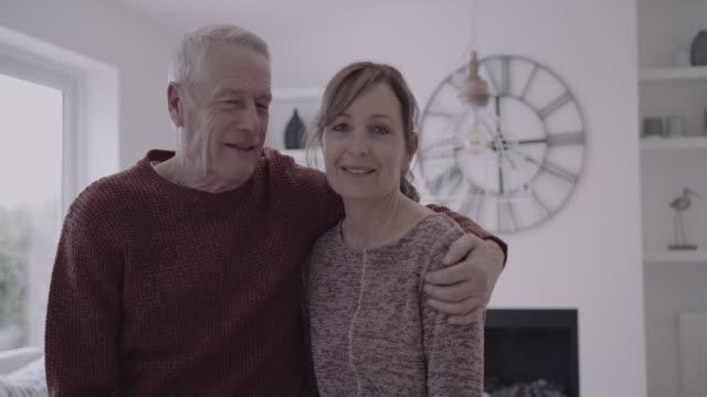 vidéos et rushes de portrait of senior adult couple embracing at home in living room - affectueux