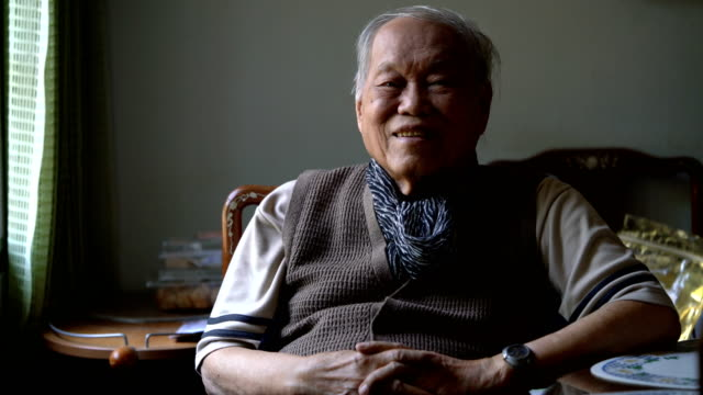 portrait of senior asian man sitting in dark room with window light - over 80 stock videos and b-roll footage