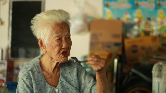 portrait of senior asian woman, thai ethnicity, eating rice - video portrait stock videos & royalty-free footage