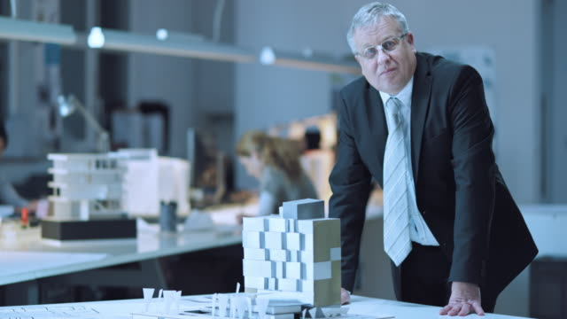 DS Portrait of senior business man with building model