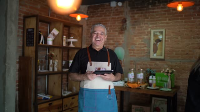 vídeos de stock e filmes b-roll de portrait of senior business owner looking at camera - loja de roupa