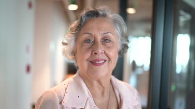portrait of senior businesswoman at corridor office - senior women stock videos & royalty-free footage