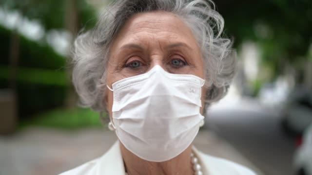 vídeos de stock e filmes b-roll de portrait of senior businesswoman with mask - vestuário para proteção