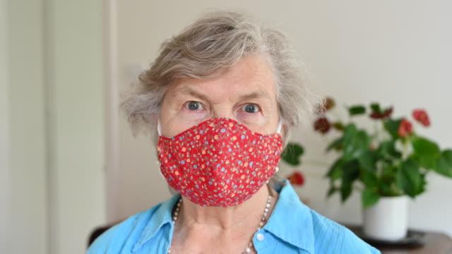 stockvideo's en b-roll-footage met portret van hogere kaukasische vrouw die huisgemaakt masker op haar gezicht plaatst - 70 79 jaar