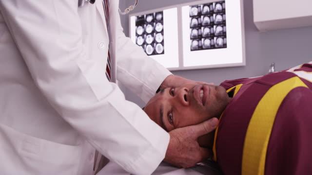 vídeos de stock, filmes e b-roll de portrait of senior chiropractor consult sports athlete's neck injury - physical injury