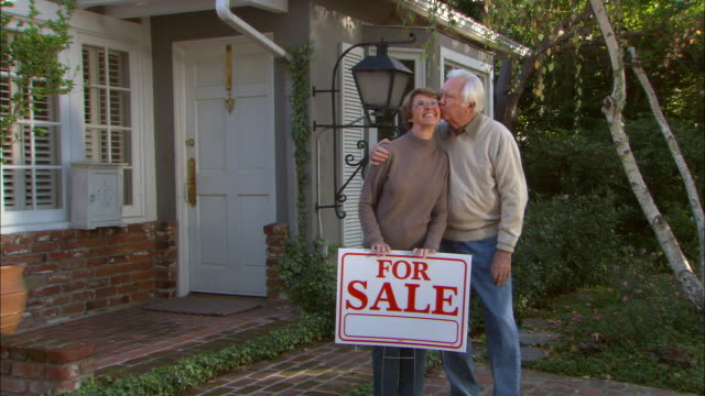 zi, ms, portrait of senior couple in front of house with  for sale sign, los angeles, california, usa - in front of stock videos & royalty-free footage