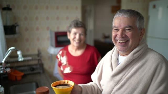 vídeos y material grabado en eventos de stock de retrato de pareja mayor preparando café en casa - oler