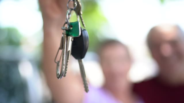 portrait of senior couple showing car key in front of they new car - grey hair stock videos & royalty-free footage