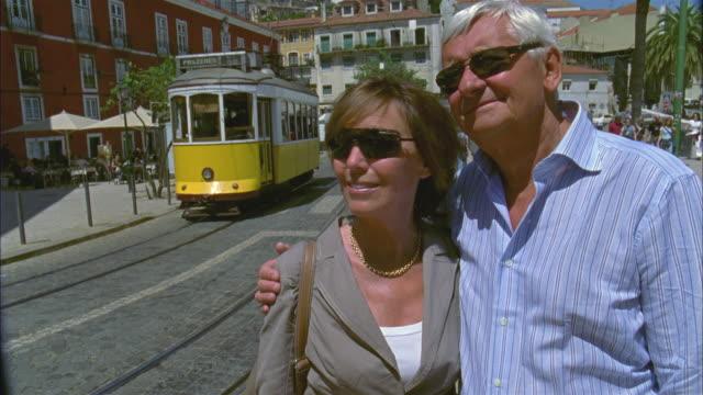 CU, Portrait of senior couple standing on street, tram in background, Alfama, Lisbon, Portugal
