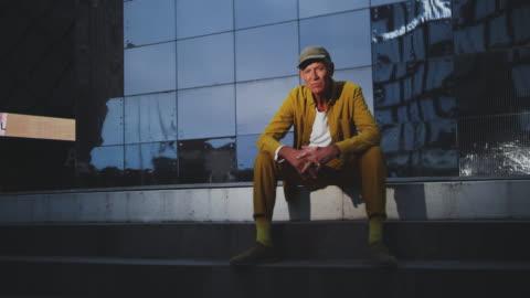 vídeos y material grabado en eventos de stock de portrait of senior creative businessman sitting outside office building - guay
