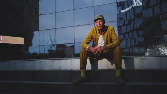 portrait of senior creative businessman sitting outside office building - cool und lässig stock-videos und b-roll-filmmaterial