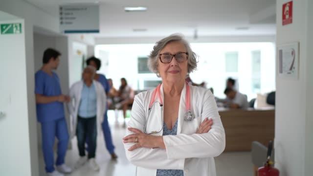 vídeos y material grabado en eventos de stock de retrato de una doctora de alto rango en el hospital - brazos cruzados