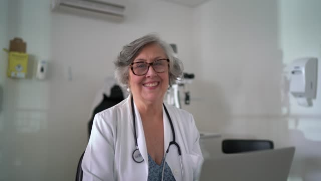portrait of senior female doctor using laptop at doctor's office - lab coat stock videos & royalty-free footage