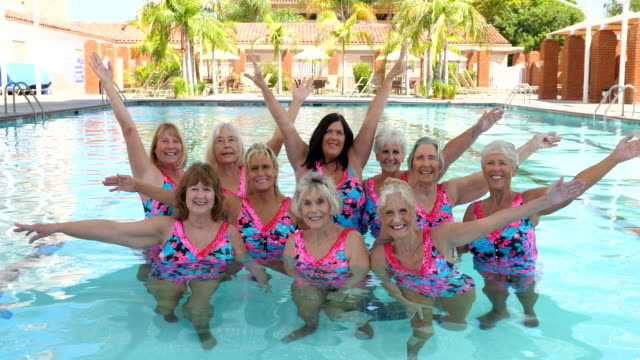 ms portrait of senior female synchronized swim team standing in pool with arms raised - vibrant color stock videos & royalty-free footage
