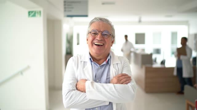 vídeos y material grabado en eventos de stock de retrato de un médico varón de alto rango en el hospital - bata de laboratorio