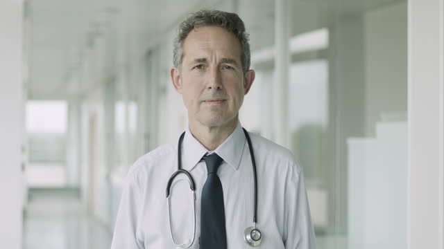 portrait of senior male doctor standing in hospital corridor looking at camera with stethoscope - shirt and tie stock videos & royalty-free footage