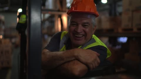 portrait of senior male worker driving forklift at warehouse - work helmet stock videos & royalty-free footage