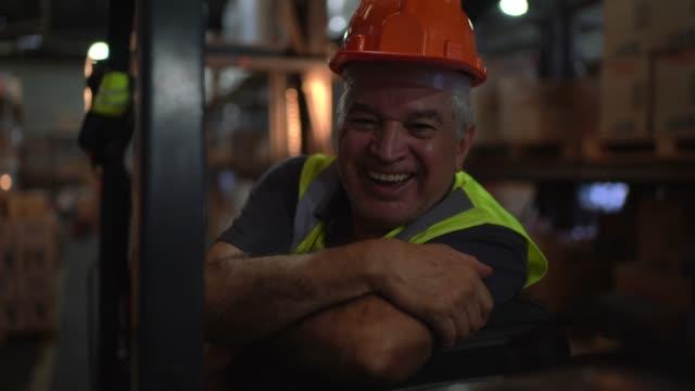 stockvideo's en b-roll-footage met portret van hogere mannelijke arbeider die vorkheftruck bij pakhuis drijft - werkhelm