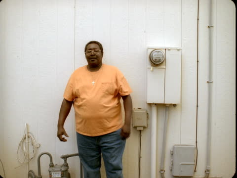 MS, Portrait of senior man against white wall with water meters, Reno, Nevada, USA