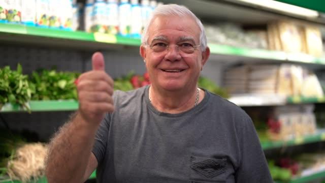 vídeos de stock, filmes e b-roll de retrato de idoso no supermercado fazendo gesto positivo - expressar otimismo