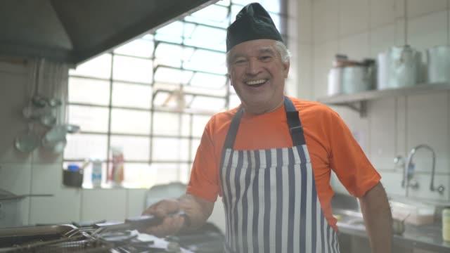 vídeos de stock, filmes e b-roll de retrato de cozimento do homem sênior na cozinha comercial - avental
