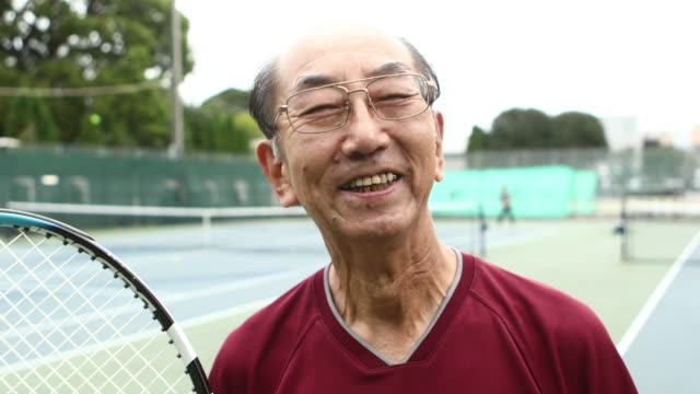 portrait of senior man enjoying tennis - 表す点の映像素材/bロール