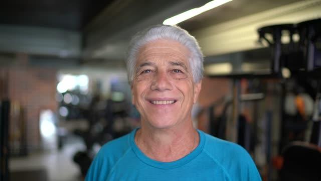 vídeos de stock e filmes b-roll de portrait of senior man exercising in gym - atleta