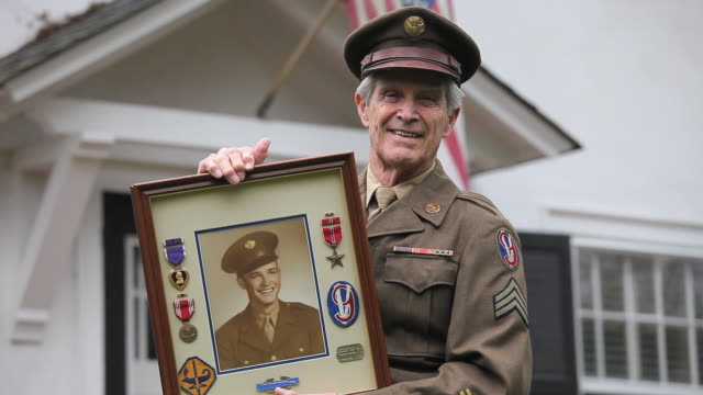 ms portrait of senior man in military uniform standing in front of home / richmond, virginia, usa. - medal stock videos & royalty-free footage