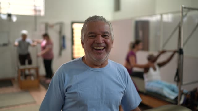 portrait of senior man in physiotherapy clinic - chiropractic adjustment stock videos & royalty-free footage