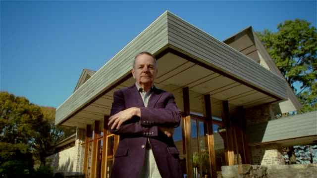 portrait of senior man in purple blazer standing in front of modern house - einzelner senior stock-videos und b-roll-filmmaterial