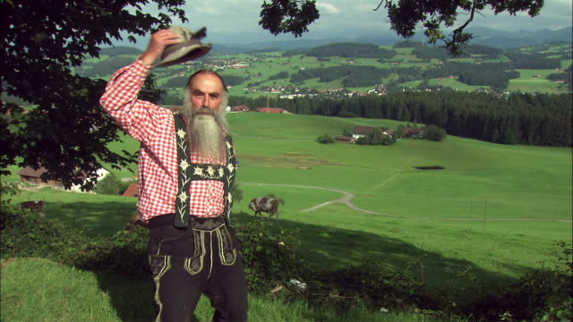 ms portrait of senior man in traditional bavarian clothing in rural landscape, bavaria, germany - baviera video stock e b–roll